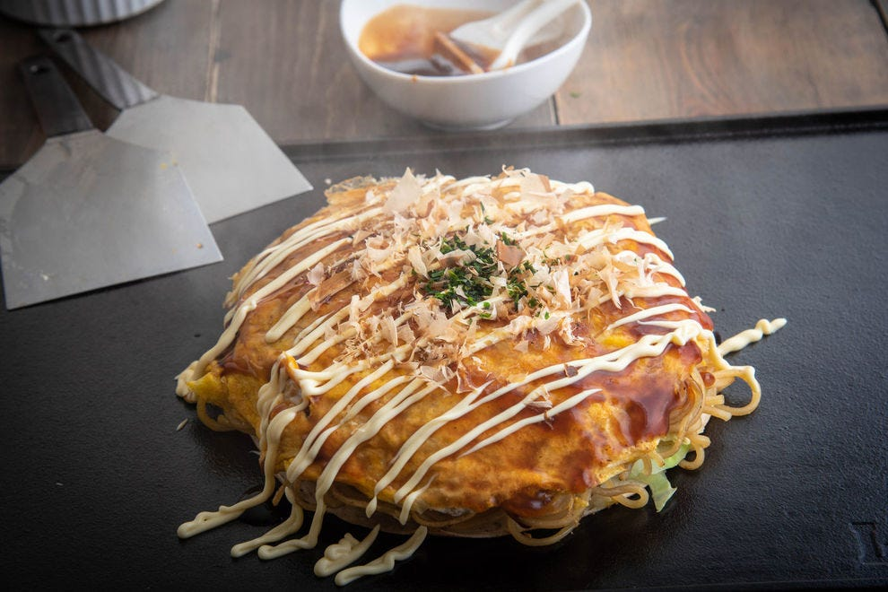 The Hiroshima-style okonomiyaki layers each of the ingredients onto the pancake whereas the Osaka-style okonomiyaki mixes all of the ingredients together