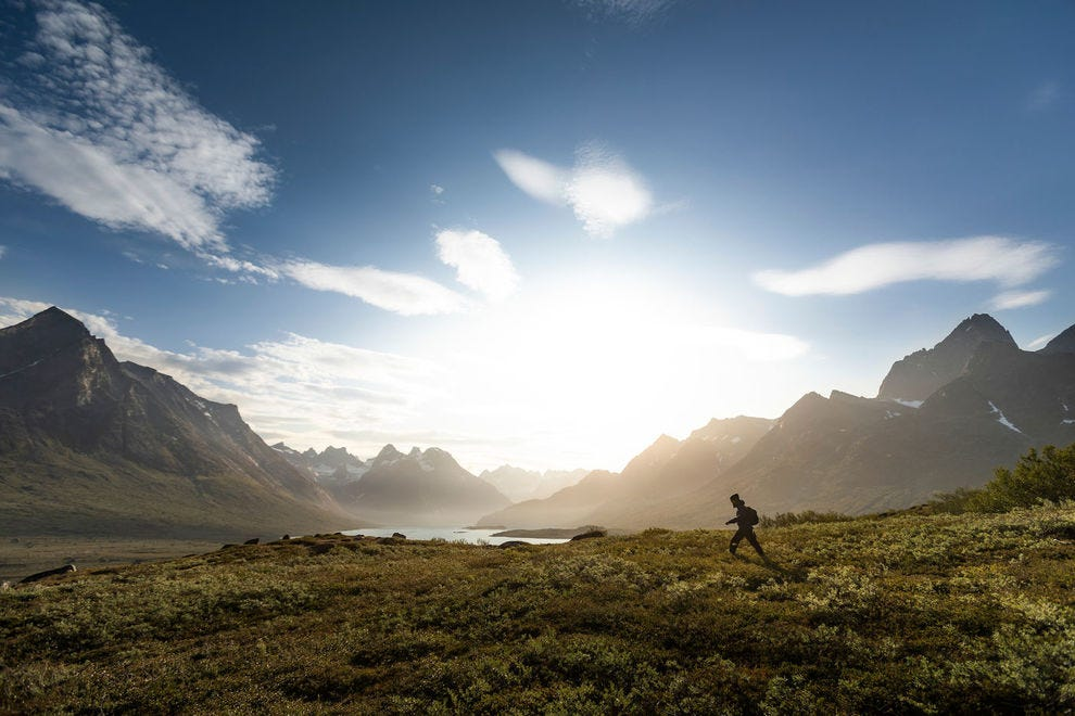 A hiker at the Tasermiut fjord surrounded by mountains