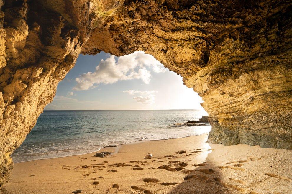 Le soleil jette un coup d'œil à travers les rochers à Cupecoy