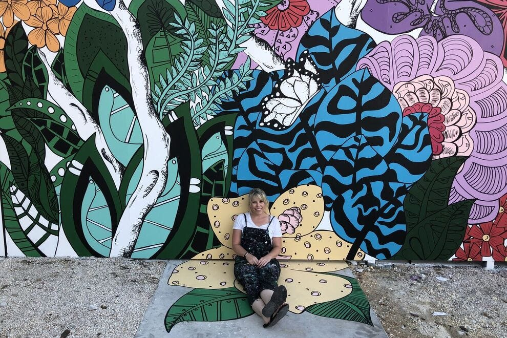 Courtney Montague sits in front of the Wynwood Walls mural in Miami