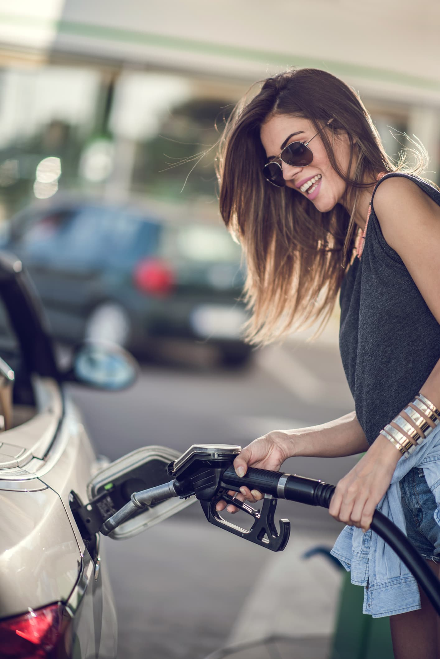Young happy woman pumping gas at gas station.